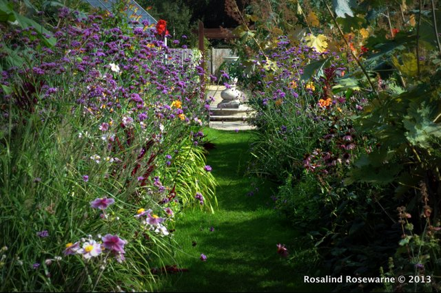 Swathes of loose summer planting flop towards the once wide grass path